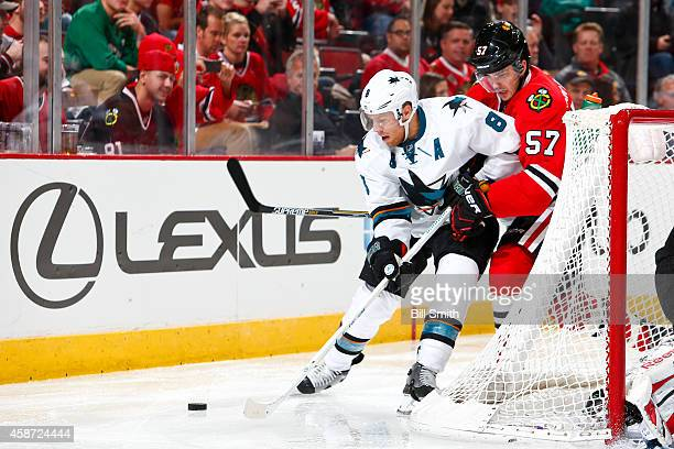 Jason Demers of the San Jose Sharks and Trevor van Riemsdyk of the Chicago Blackhawks skate behind the goal during the NHL game on November 09 2014...