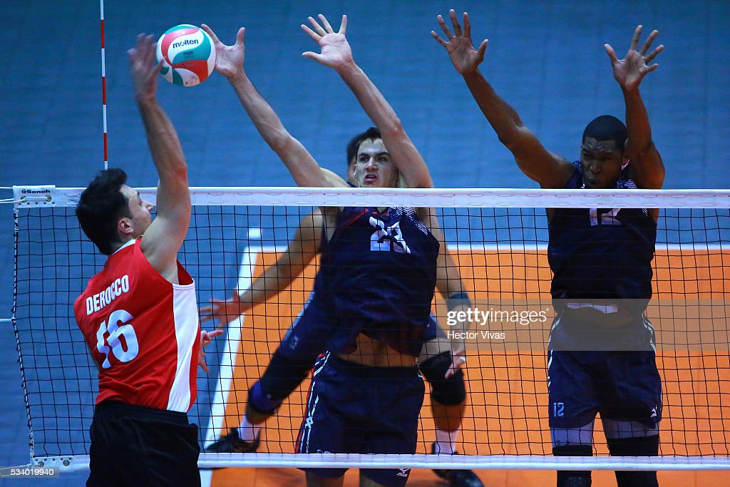 Jason Derocco of Canada spikes the ball against Torey Defalco and Kristopher Johnson of United States during a match between USA and Canada as part of Men's Panamerican Volleybal Cup at Gimnasio Ol'mpico Juan de la Barrera on May 24, 2016 in Mexico City, Mexico.