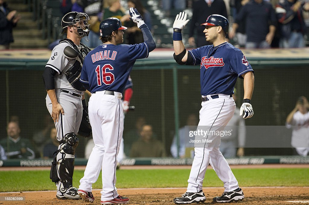 Jason Donald #16 celebrates with Travis Hafner #48 of the Cleveland Indians after Hafner hit a two run home run during the ninth inning against the Chicago White Sox at Progressive Field on October 2, 2012 in Cleveland, Ohio.