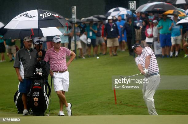 Jason Dufner of the United States plays a shot as Justin Thomas looks on during a practice round prior to the 2017 PGA Championship at Quail Hollow...