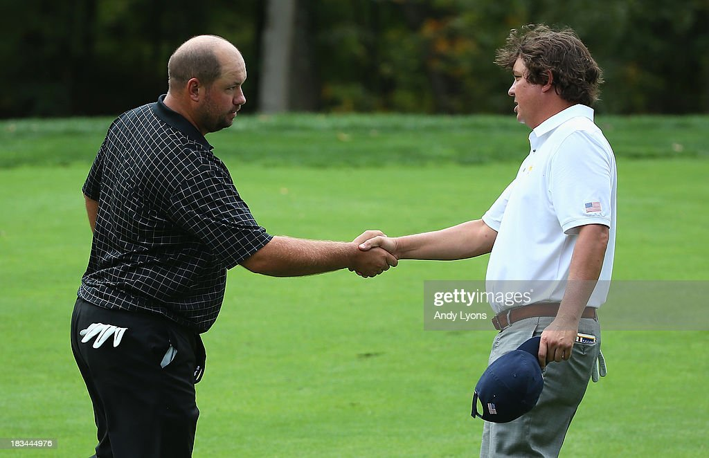 Jason Dufner of the U.S. Team (L) shakes hands with Brendon de Jonge of South Africa and the International Team on the 15th green after Dufner won the match 4&3 during the Day Four Singles Matches at the Muirfield Village Golf Club on October 6, 2013 in Dublin, Ohio.