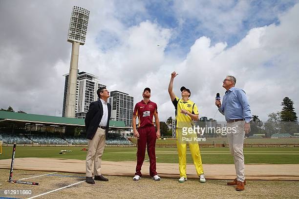 Jason Floros of the Bulls and Adam Voges of the Warriors attend the coin toss with match referee Steve Bernard and television commentator Tom Moody...
