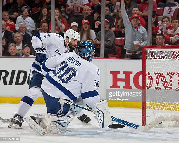 Jason Garrison and goalie Ben Bishop of the Tampa Bay Lightning reach back for a puck that scored on a flipping shot from Joakim Andersson of the...