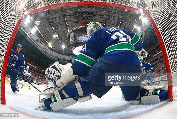 Jason Garrison eyes the loose puck after Eddie Lack of the Vancouver Canucks make a save against the Winnipeg Jets during their NHL game at Rogers...