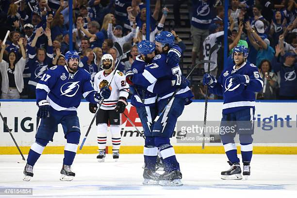 Jason Garrison of the Tampa Bay Lightning celebrates with teammate Victor Hedman after scoring a third period goal against Corey Crawford of the...