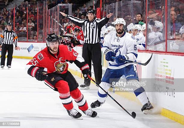 Jason Garrison of the Tampa Bay Lightning flips the puck past Erik Karlsson of the Ottawa Senators at Canadian Tire Centre on October 22 2016 in...