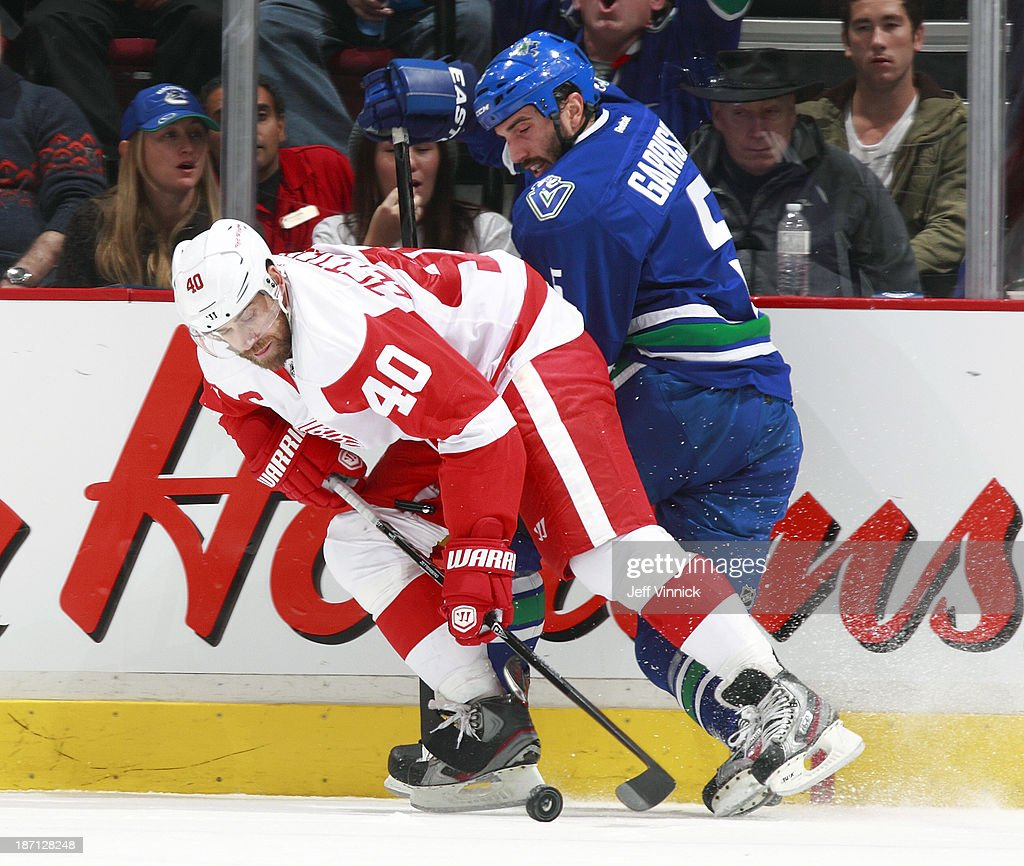 Jason Garrison #5 of the Vancouver Canucks and Henrik Zetterberg #40 of the Detroit Red Wings battle for the puck during their NHL game at Rogers Arena on October 30, 2013 in Vancouver, British Columbia, Canada. Detroit won 2-1.