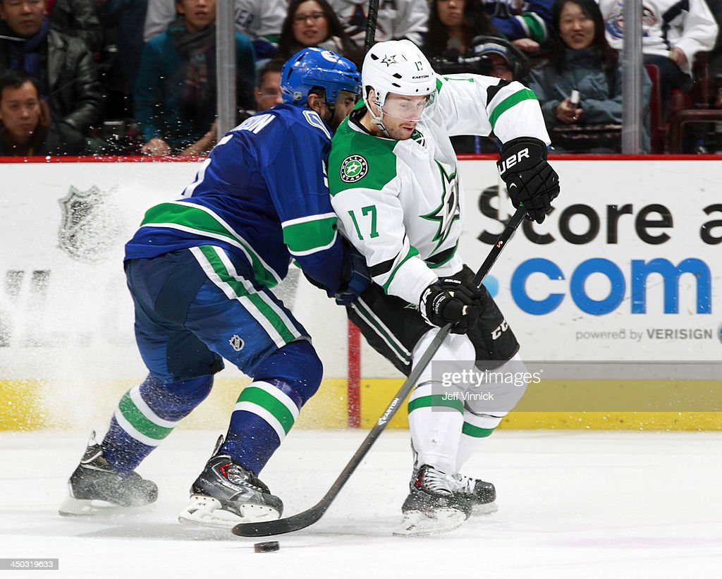 Jason Garrison #5 of the Vancouver Canucks and Rich Peverley #17 of the Dallas Stars battle for the puck during their NHL game at Rogers Arena on November 17, 2013 in Vancouver, British Columbia, Canada. Dallas won 2-1.