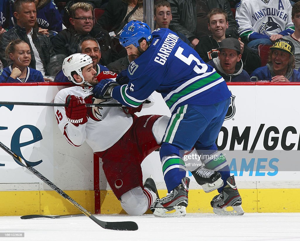 Jason Garrison #5 of the Vancouver Canucks checks Boyd Gordon #15 of the Phoenix Coyotes during their NHL game at Rogers Arena April 8, 2013 in Vancouver, British Columbia, Canada.