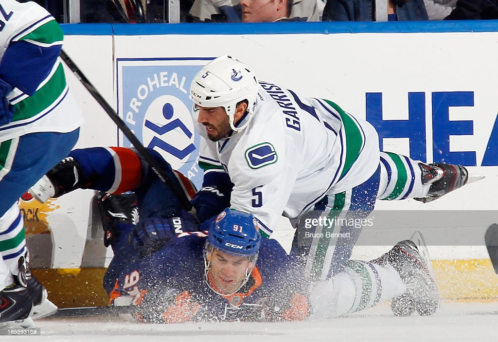 <a gi-track='captionPersonalityLinkClicked' href=/galleries/search?phrase=Jason+Garrison&family=editorial&specificpeople=2143635 ng-click='$event.stopPropagation()'>Jason Garrison</a> #5 of the Vancouver Canucks checks <a gi-track='captionPersonalityLinkClicked' href=/galleries/search?phrase=John+Tavares&family=editorial&specificpeople=601791 ng-click='$event.stopPropagation()'>John Tavares</a> #91 of the New York Islanders to the ice during the first period at the Nassau Veterans Memorial Coliseum on October 22, 2013 in Uniondale, New York.