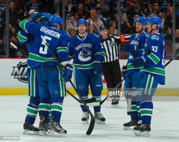 Jason Garrison of the Vancouver Canucks is congratulated by teammates Daniel Sedin Henrik Sedin and Jannik Hansen after scoring against the Anaheim...