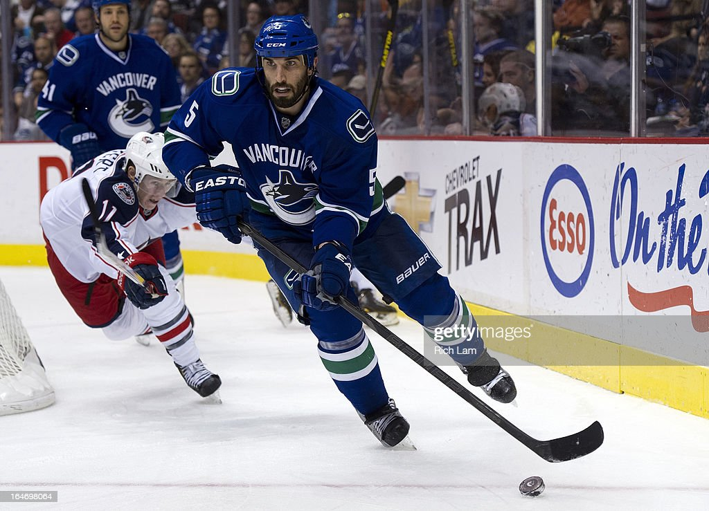 <a gi-track='captionPersonalityLinkClicked' href=/galleries/search?phrase=Jason+Garrison&family=editorial&specificpeople=2143635 ng-click='$event.stopPropagation()'>Jason Garrison</a> #5 of the Vancouver Canucks looks to make a pass while being checked by Matt Calvert #11 of the Columbus Blue Jackets during the third period in NHL action on March 26, 2013 at Rogers Arena in Vancouver, British Columbia, Canada.