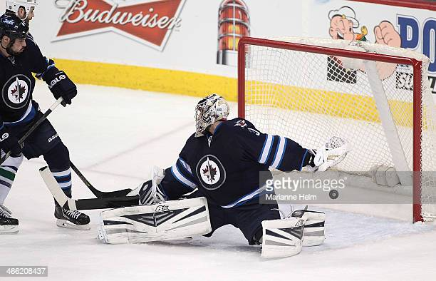 Jason Garrison of the Vancouver Canucks scores against Ondrej Pavelec of the Winnipeg Jets in third period action in an NHL game at the MTS Centre on...