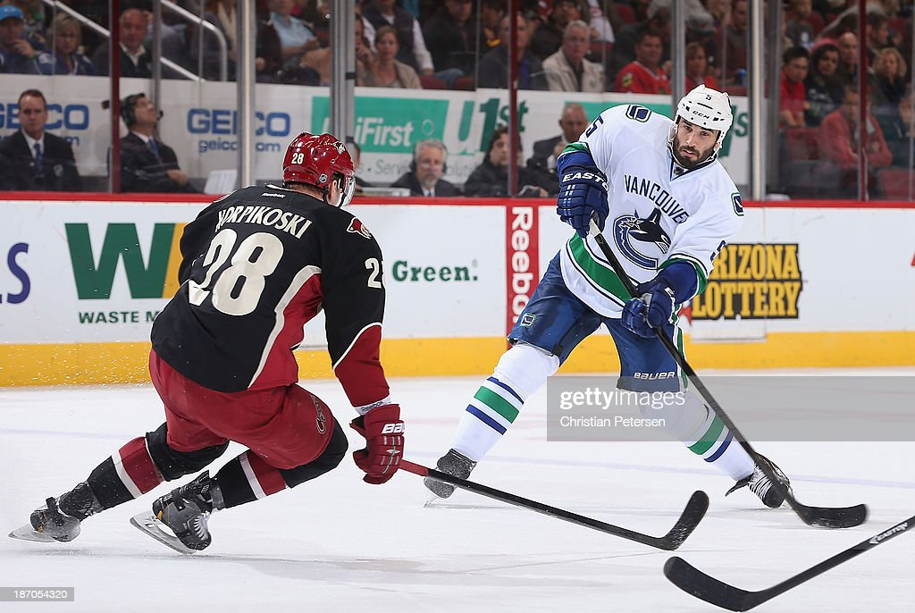 <a gi-track='captionPersonalityLinkClicked' href=/galleries/search?phrase=Jason+Garrison&family=editorial&specificpeople=2143635 ng-click='$event.stopPropagation()'>Jason Garrison</a> #5 of the Vancouver Canucks shoots the puck defended by <a gi-track='captionPersonalityLinkClicked' href=/galleries/search?phrase=Lauri+Korpikoski&family=editorial&specificpeople=2108074 ng-click='$event.stopPropagation()'>Lauri Korpikoski</a> #28 of the Phoenix Coyotes during the NHL game at Jobing.com Arena on November 5, 2013 in Glendale, Arizona. The Coyotes defeated the Canucks 3-2 in an overtime shoot out.