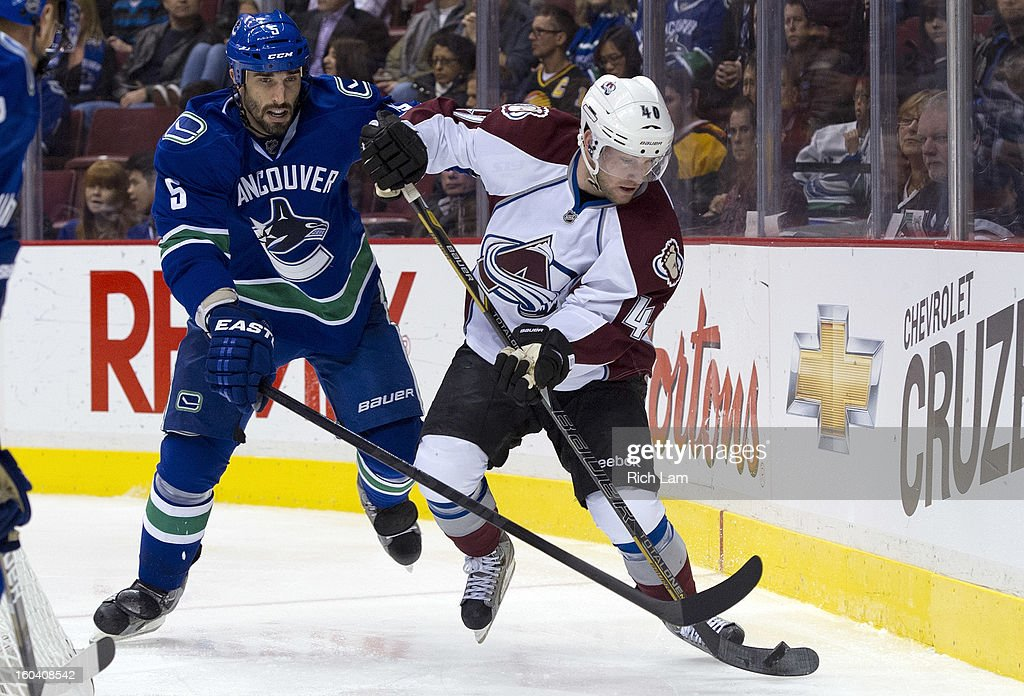 <a gi-track='captionPersonalityLinkClicked' href=/galleries/search?phrase=Jason+Garrison&family=editorial&specificpeople=2143635 ng-click='$event.stopPropagation()'>Jason Garrison</a> #5 of the Vancouver Canucks tries to check Mark Olver #40 of the Colorado Avalanche off the puck during the third period in NHL action on January 30, 2013 at Rogers Arena in Vancouver, British Columbia, Canada.