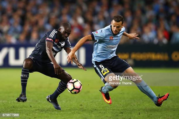Jason Geria of the Victory competes with Bobo of Sydney during the 2017 ALeague Grand Final match between Sydney FC and the Melbourne Victory at...