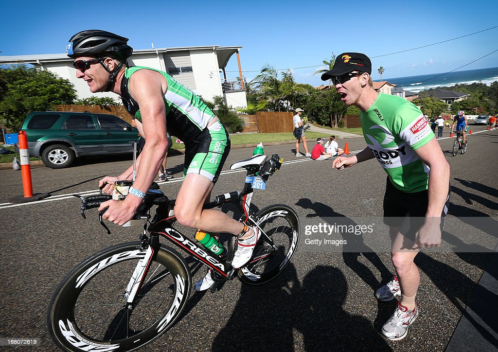 Jason Gerke of Australia (left) digs deep as he battles the steepest hill in the Ironman, on Matthew Flinders Drive Port Macquarie, during the race in the Port Macquarie round of the 2013 Ironman Australia series on May 5, 2013 in Port Macquarie, Australia.