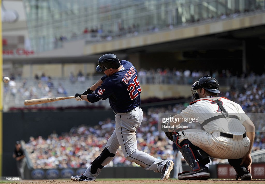 <a gi-track='captionPersonalityLinkClicked' href=/galleries/search?phrase=Jason+Giambi&family=editorial&specificpeople=194953 ng-click='$event.stopPropagation()'>Jason Giambi</a> #25 of the Cleveland Indians hits a three run home run as <a gi-track='captionPersonalityLinkClicked' href=/galleries/search?phrase=Joe+Mauer&family=editorial&specificpeople=214614 ng-click='$event.stopPropagation()'>Joe Mauer</a> #7 of the Minnesota Twins catches during the seventh inning of the game on August 14, 2013 at Target Field in Minneapolis, Minnesota.