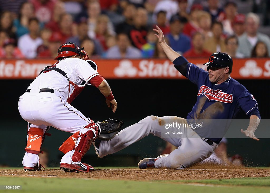 <a gi-track='captionPersonalityLinkClicked' href=/galleries/search?phrase=Jason+Giambi&family=editorial&specificpeople=194953 ng-click='$event.stopPropagation()'>Jason Giambi</a> #41 of the Cleveland Indians is tagged out at home by catcher <a gi-track='captionPersonalityLinkClicked' href=/galleries/search?phrase=Hank+Conger&family=editorial&specificpeople=713039 ng-click='$event.stopPropagation()'>Hank Conger</a> #16 of the Los Angeles Angels of Anaheim in the sixth inning at Angel Stadium of Anaheim on August 19, 2013 in Anaheim, California.