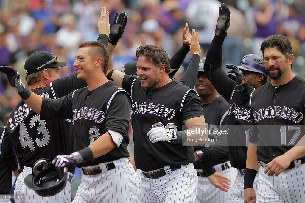 Jason Giambi of the Colorado Rockies and his teammates celebrate his game winning three run pinch hit walk off home run off of Scott Elbert of the...