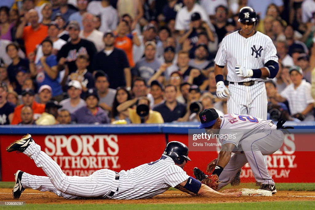 Jason Giambi of the New York Yankees is tagged out by Julio Franco of the New York Mets in the first inning at Yankee Stadium on July 2 2006 in New...