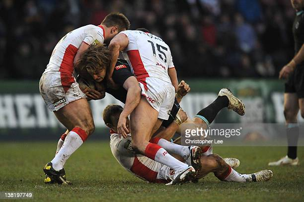 Jason Golden of Broncos is stopped by Paul Clough Josh Perry and Mark Flanagan of St Helens during the Stobart Super League match between London...