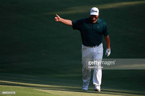 Jason Gore acknowledges fans as he walks up the 17th hole during the final round of the Wyndham Championship at Sedgefield Country Club on August 23...