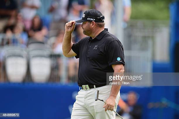 Jason Gore reacts after making his birdie putt on the 18th green during the third round of the Wyndham Championship at Sedgefield Country Club on...