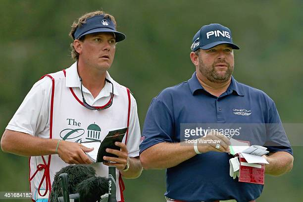 Jason Gore talks with his caddy on the second tee during the second round of the Greenbrier Classic at the Old White TPC on July 4 2014 in White...