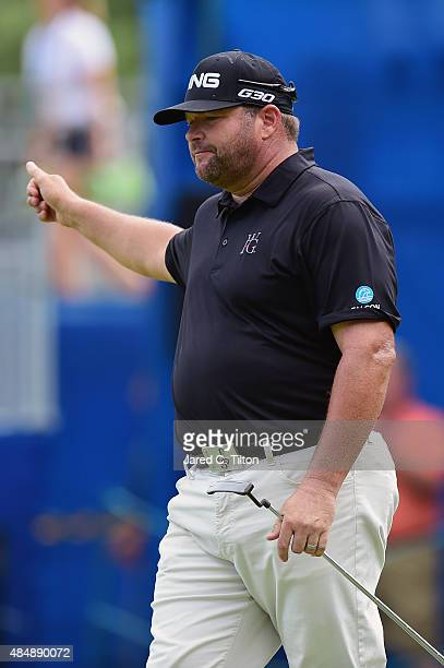 Jason Gore waves to the gallery after making his birdie putt on the 18th green during the third round of the Wyndham Championship at Sedgefield...