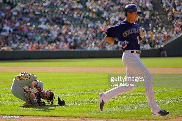 Jason Grilli of the Atlanta Braves falls to the ground in pain after injuring his ankle running to cover first base on an infield single by Drew...