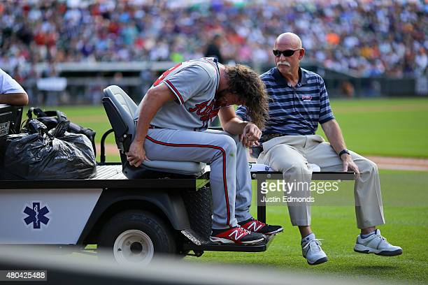 Jason Grilli of the Atlanta Braves is carted off the field with a member of the training staff after injuring his ankle running to cover first base...