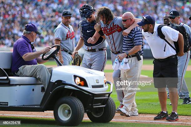 Jason Grilli of the Atlanta Braves is helped to the cart by catcher Ryan Lavarnway and a member of the training staff after injuring his ankle...