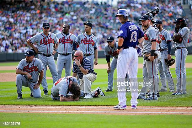 Jason Grilli of the Atlanta Braves lies on the ground and is attended to by the training staff after injuring his ankle running to cover first base...