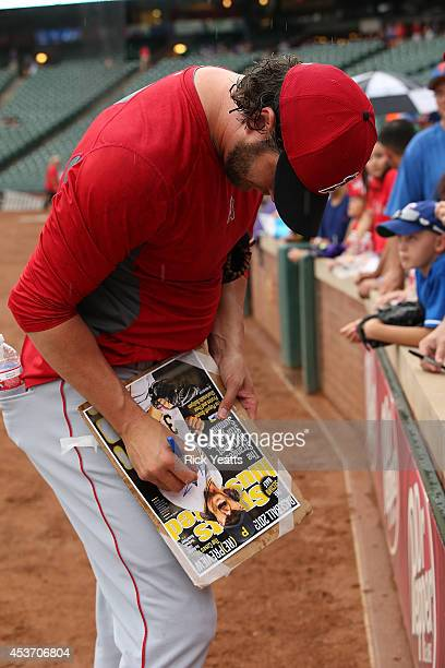Jason Grilli of the Los Angeles Angels of Anaheim signs autographs before the start of the game against the Texas Rangers at Globe Life Park in...