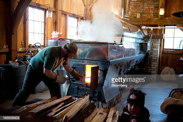 Jason Grossman loads wood into a wood burner while boiling maple sap in the evaporator in the sugar shack at Grossman Brothers Maple Products in...