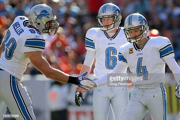 Jason Hanson of the Detroit Lions celebrates his 50yard field goal with teammate Will Heller against the Denver Broncos during the second quarter at...