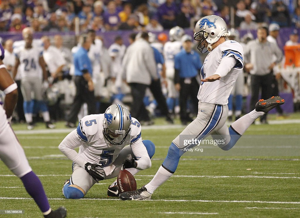 Jason Hanson #4 of the Detroit Lions kicks a field goal with a hold from Nick Harris #5 on November 11, 2012 at Mall of America Field at the Hubert H. Humphrey Metrodome in Minneapolis, Minnesota.