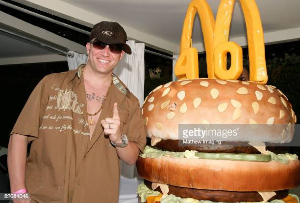 Jason Harper poses beside a giant 'Big Mac' burgerthemed birthday cake during the McDonald's Big Mac 40th Birthday Party at Project Beach House in...