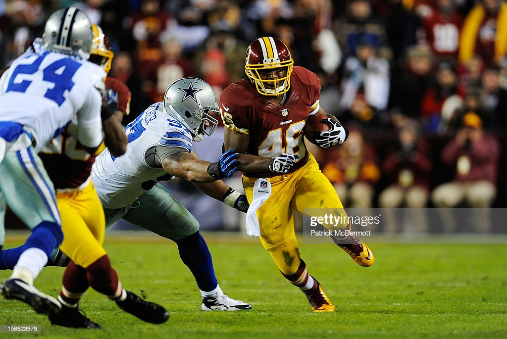 Jason Hatcher #97 of the Dallas Cowboys tries to tackle Alfred Morris #46 of the Washington Redskins in the third quarter at FedExField on December 30, 2012 in Landover, Maryland.
