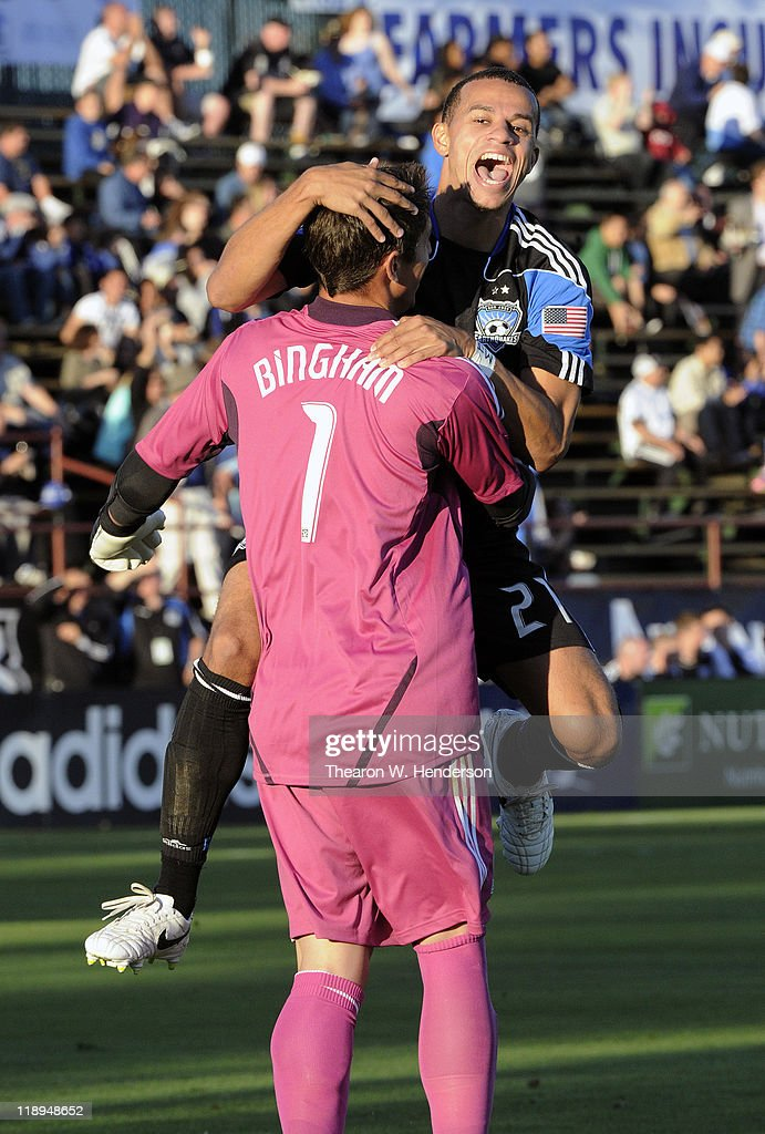 Jason Hernandez of the San Jose Earthquakes celebrates with goalkeeper David Bingham after Bingham kicked the ball the length of the field and scored...