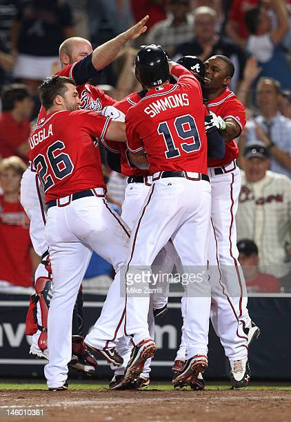 Jason Heyward of the Atlanta Braves is mobbed by teammates Dan Uggla Michael Bourn Brian McCann and Andrelton Simmons after Heyward scored the...