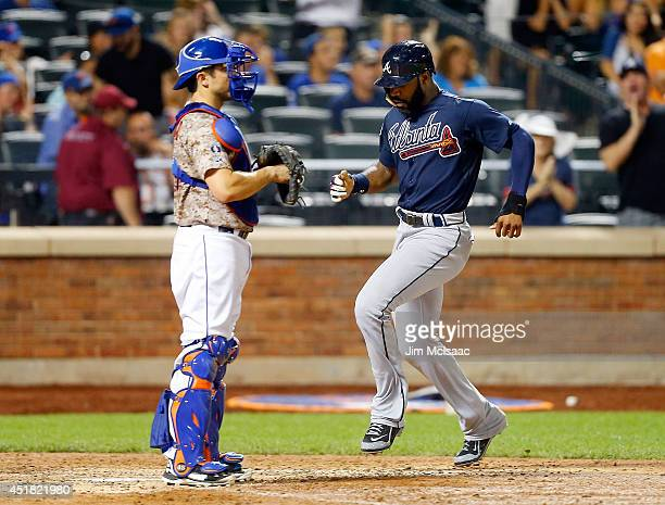 Jason Heyward of the Atlanta Braves scores an eighthinning run past Travis d'Arnaud of the New York Mets at Citi Field on July 7 2014 in the Flushing...