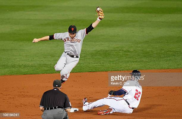 Jason Heyward of the Atlanta Braves slides in safely under a leaping Freddy Sanchez of the San Francisco Giants in the second inning during Game Four...
