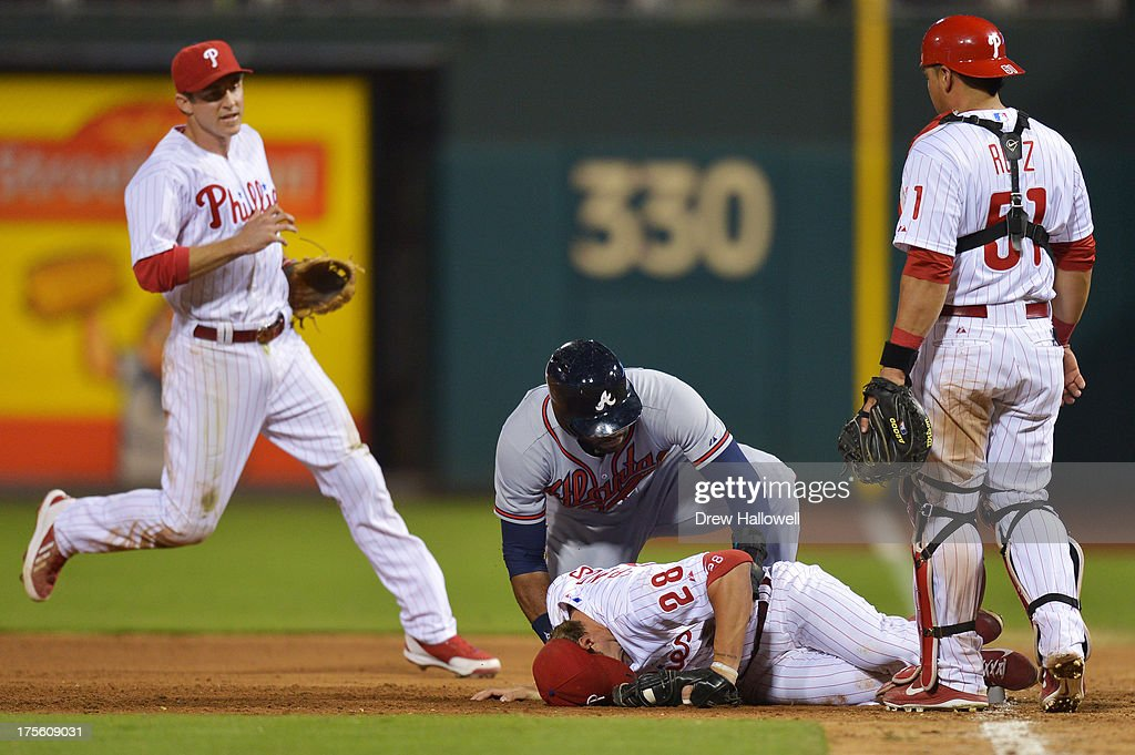 <a gi-track='captionPersonalityLinkClicked' href=/galleries/search?phrase=Jason+Heyward&family=editorial&specificpeople=5043351 ng-click='$event.stopPropagation()'>Jason Heyward</a> #22 of the Atlanta Braves tries to help up <a gi-track='captionPersonalityLinkClicked' href=/galleries/search?phrase=Kevin+Frandsen&family=editorial&specificpeople=3982842 ng-click='$event.stopPropagation()'>Kevin Frandsen</a> #28 of the Philadelphia Phillies after a collision in the sixth inning during a rundown at Citizens Bank Park on August 4, 2013 in Philadelphia, Pennsylvania. Chase Utley #26 and Carlos Ruiz #51 look on.