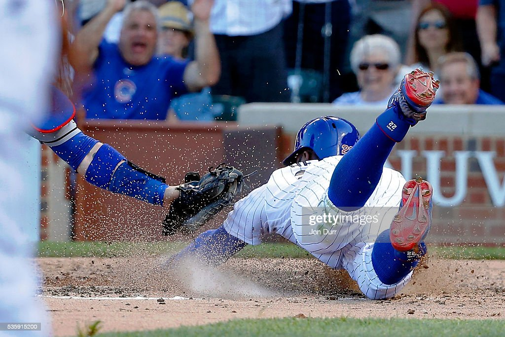 Jason Heyward #22 of the Chicago Cubs beats the tag of Yasmani Grandal #9 of the Los Angeles Dodgers to score off of an RBI double by Anthony Rizzo #44 (not pictured) against the Los Angeles Dodgers during the fifth inning at Wrigley Field on May 30, 2016 in Chicago, Illinois.