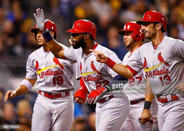 Jason Heyward of the St Louis Cardinals is congratulated at home plate by teammate Matt Carpenter after hitting a grand slam home run in the third...