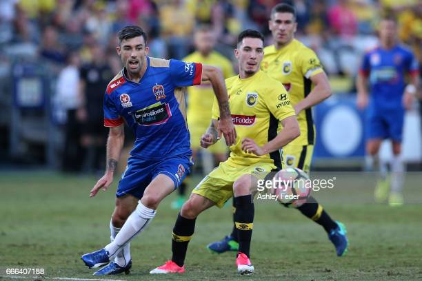 Jason Hoffman of the Jets contests the ball against Storm Roux of the Mariners during the round 26 ALeague match between the Central Coast Mariner...