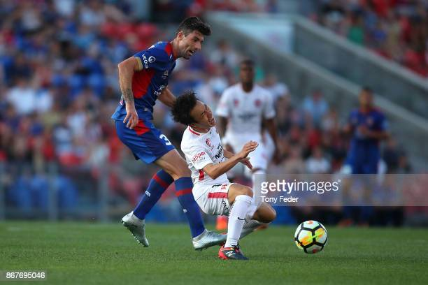 Jason Hoffman of the Jets contests the ball with Jumpei Kusukami of the Wanderers round four ALeague match between the Newcastle Jets and the Western...