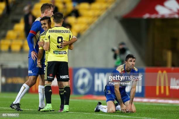 Jason Hoffman of the Jets reacts after scoring an own goal while Kosta Barbarouses and Sarpreet Singh of the Phoenix celebrate during the round 24...